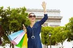 Mulher com os sacos de compras e o smartphone que acenam com mão fotos de stock royalty free