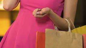 Mulher com os sacos de compras no braço que fala sobre o telefone celular, shopaholic, close-up vídeos de arquivo