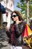 Mulher com os sacos de compras no ombro usando o telefone celular Fotografia de Stock