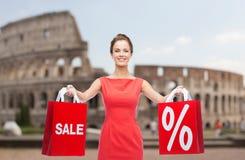 Mulher com os sacos de compras vermelhos sobre o coliseu Imagens de Stock