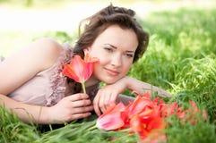 Mulher com os tulips da mola vermelha em um jardim imagens de stock