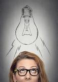 Mulher com os vidros que têm uma ideia que olha acima foto de stock
