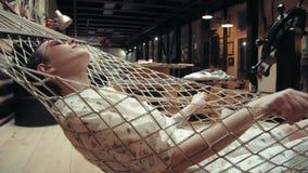 Mulher com os vidros vestindo do cabelo curto que relaxam na rede em seu apartamento do sótão