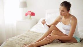 Mulher com pés desencapados tocantes da pena na cama filme