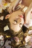 Mulher com pétalas cor-de-rosa. fotografia de stock