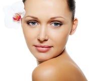 Mulher com pele desobstruída e flor perto de seus olhos Fotografia de Stock Royalty Free