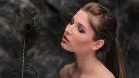 Mulher com a pena do pavão que flerta na frente da câmera vídeos de arquivo