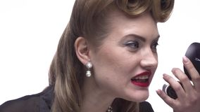 A mulher com penteado retro está olhando seus bordos no espelho, fim acima video estoque