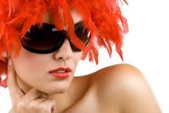 Mulher com a peruca e os óculos de sol vermelhos da pena Fotos de Stock