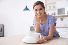 Mulher com a pilha de pratos limpos na mesa de cozinha fotos de stock royalty free