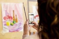 Mulher com pintura no smartphone na escola de arte Fotografia de Stock Royalty Free