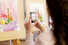 Mulher com pintura no smartphone na escola de arte Foto de Stock Royalty Free