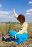 Mulher com portátil e o telefone móvel Fotografia de Stock