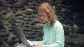 Mulher com portátil e originais no fundo de uma parede obstruir-se video estoque