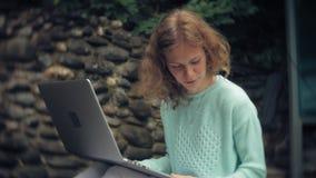 Mulher com portátil e originais no fundo de uma parede obstruir-se vídeos de arquivo