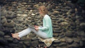 Mulher com portátil e originais no fundo de uma parede obstruir-se filme