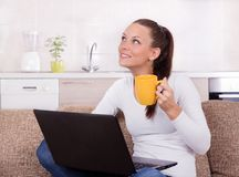 Mulher com portátil e xícara de café no sofá fotos de stock royalty free