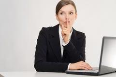 Mulher com portátil que sussurra, com segredo no escritório Foto de Stock Royalty Free
