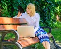 A mulher com portátil trabalha fora Senhora do negócio que resolve os problemas remotos A chamada do smartphone da menina resolve fotografia de stock