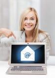 Mulher com portátil que aponta no sinal do email Imagem de Stock