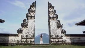Mulher com posição aberta larga dos braços na porta do templo, olhando o vulcão de Agung video estoque