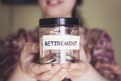 A mulher com posse bonita do sorriso um frasco plástico da aposentadoria para salvar o dinheiro Imagem de Stock