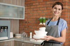 Mulher com pratos e os copos limpos foto de stock