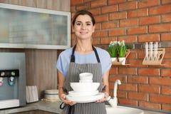 Mulher com pratos e os copos limpos fotografia de stock