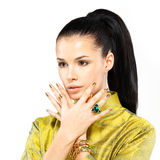 Mulher com pregos dourados e esmeralda da pedra preciosa Fotografia de Stock