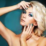 Mulher com pregos verdes e composição do encanto dos olhos imagem de stock