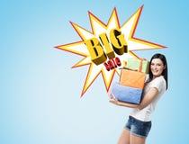 Mulher com presentes perto de uma parede azul com o cartaz grande da venda Imagem de Stock Royalty Free