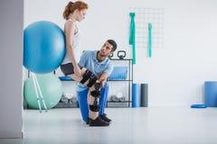 Mulher com problema ortopédico que exercita com bola fotografia de stock