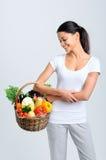 Mulher com produtos frescos crus em uma cesta Fotografia de Stock Royalty Free