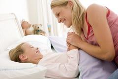 Mulher com a rapariga no sorriso da cama Fotografia de Stock