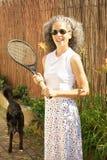 Mulher com raquete e cão de tênis imagens de stock