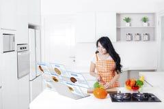 Mulher com receitas virtuais do alimento na cozinha Imagem de Stock
