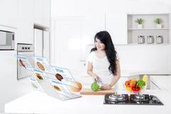 Mulher com receitas virtuais e portátil em casa imagens de stock