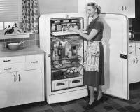 Mulher com refrigerador aberto (todas as pessoas descritas não são umas vivas mais longo e nenhuma propriedade existe Garantias d Imagens de Stock Royalty Free