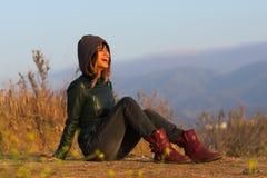 Mulher com revestimento e botas assentadas no riso à terra Imagens de Stock