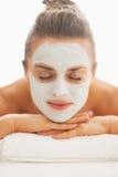 Mulher com revitalizar a máscara na cara que coloca na tabela da massagem imagem de stock royalty free