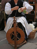 mulher com a roda de giro de madeira ao girar um fio foto de stock