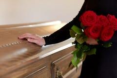 Mulher com rosas vermelhas e caixão no funeral imagens de stock