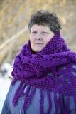 A mulher com roxo fez malha o xaile em seus ombros Imagens de Stock