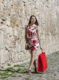 Mulher com saco de compras vermelho em uma cidade Fotos de Stock