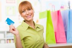 Mulher com sacos de compras coloridos e guardar um cartão de crédito Foto de Stock