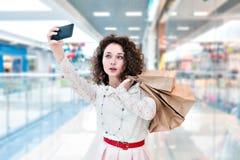 Mulher com sacos de compras e fatura de um selfie Imagem de Stock Royalty Free