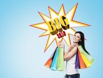 Mulher com sacos de compras múltiplos perto de um cartaz grande da venda em um bl Imagem de Stock Royalty Free