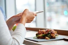 Mulher com salada do smartphone e do presunto no restaurante foto de stock royalty free