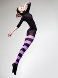 A mulher com salto perfeito do corpo vestiu-se em calças justas listradas roxas e na parte superior preta imagens de stock