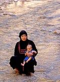A mulher com seu bebê no rio do Todra gorges em Marrocos Fotos de Stock Royalty Free